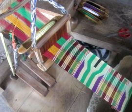 Kente cloth being woven on a traditional loom